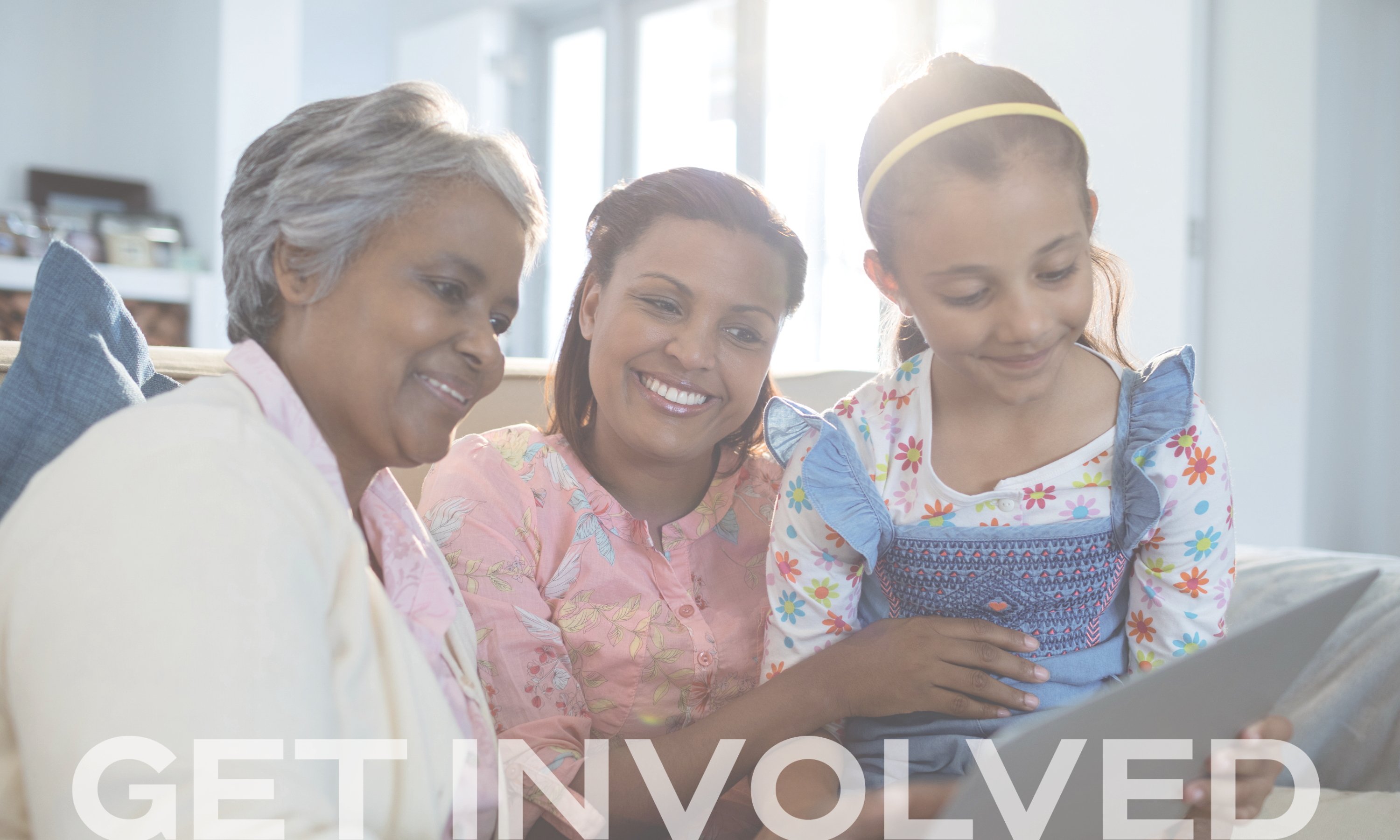 Get involved header: A family of three sit on a couch and are looking at a laptop together