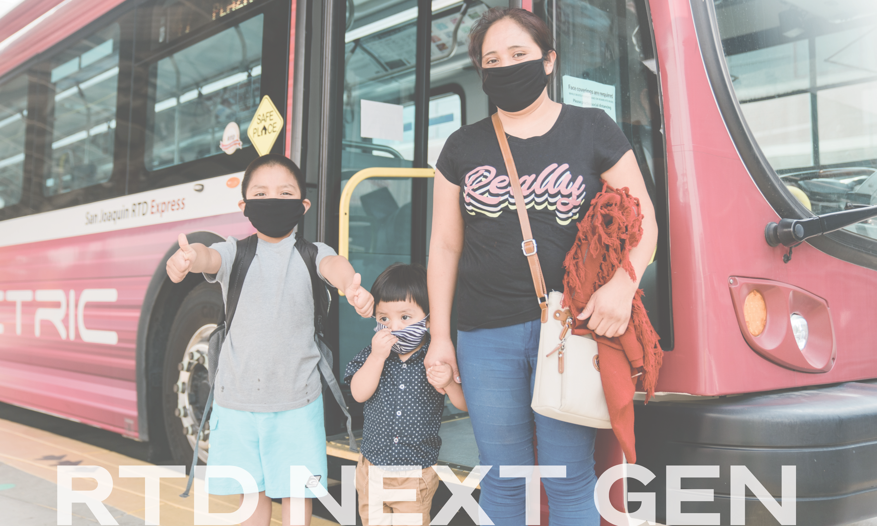 One woman in a mask and two children in masks stand in front of an RTD bus in Stockton, California.
